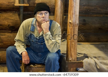 man in bib overalls sitting in his log cabin thinking about life - stock photo