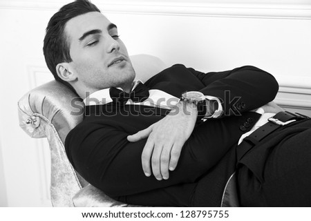 Man in black dinner jacket with bow tie. Bridegroom. Black-and-white photo. - stock photo