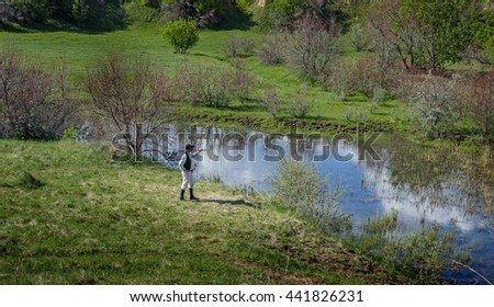 Man in black hat with a stick standing on the river bank - stock photo