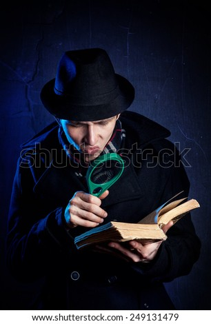 Man in black hat with magnifier glass reading the old book at dark background - stock photo