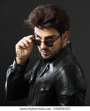 Man in black leather jacket looking over his sunglasses, studio shot, dark background - stock photo