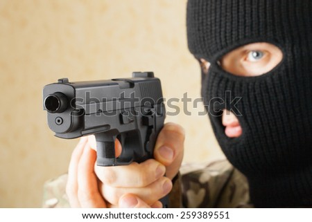 Man in black mask holding gun before him - stock photo
