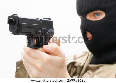 Man in black mask holding handgun - stock photo