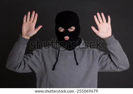 man in black mask holding hands up over grey background - stock photo