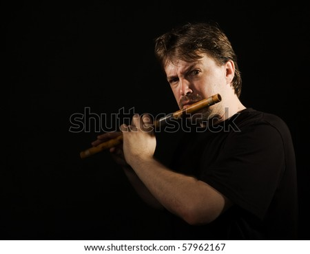 Man in black plays a wooden flute