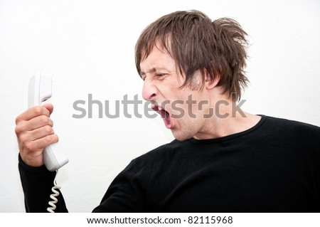 Man in black shirt screams during the conversation on the phone - stock photo