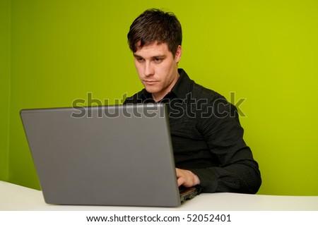 Man in black shirt working on laptop computer - stock photo