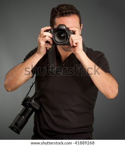 Man in black shooting with his camera with an extra one hanging from the strap - stock photo