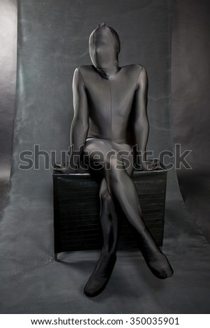 man in black skin-tight body suit and his face covered by suit . He is sitting on a black bench. Legs crossed - stock photo