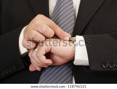 Man in black suit adjusting his watch for being in time to an important event - stock photo