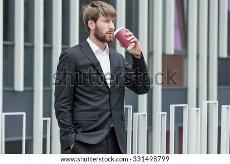 Man in black suit drinking takeaway coffee