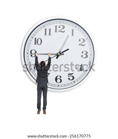 man in black suit hanging at clock hand over white background - stock photo