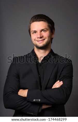 Man in Black Suit in front of a grey background looking happy