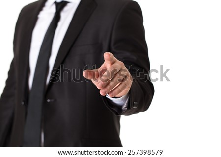 Man in black suit pushing blank virtual button on touch screen.