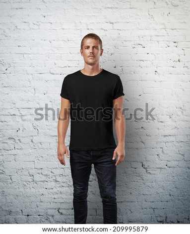 Man in black t-shirt. Brick wall background - stock photo