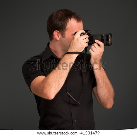 Man in black taking a picture with a photo camera - stock photo