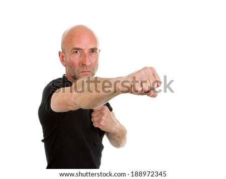 Man in black tee-shirt throwing a punch - stock photo