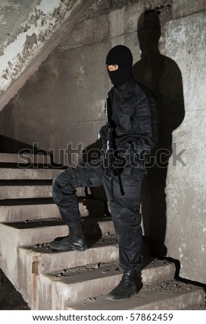 Man in black uniform holding M-16 rifle standing on stairs - stock photo