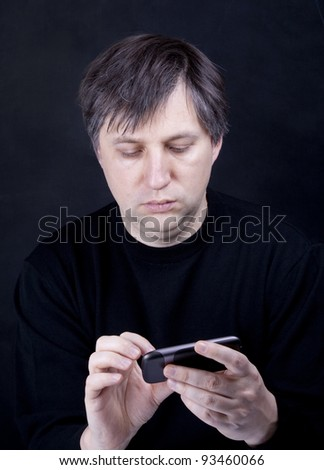 Man in black  working on smart-phone - stock photo