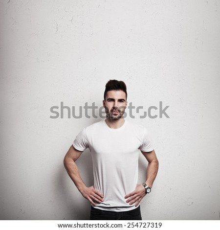 Man in blank t-shirt, white grunge wall background - stock photo