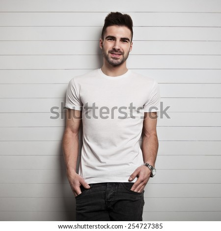 Man in blank t-shirt, wooden wall background - stock photo