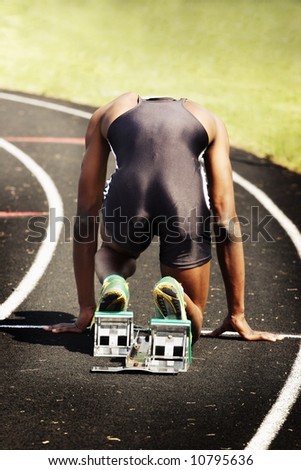 Man in blocks on the starting line of a race (main focus on shoes and blocks) - stock photo