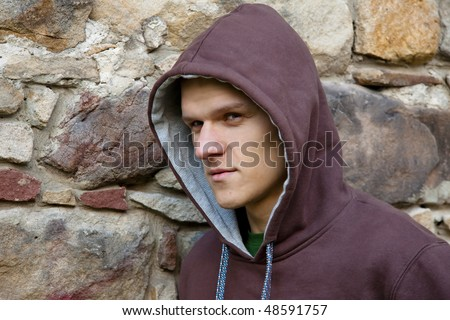 Man in blouse hooded. Next to brick wall.