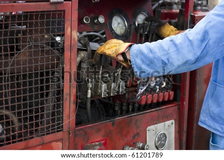 Man in blue clothes with yellow gloves operating a old machine - stock photo
