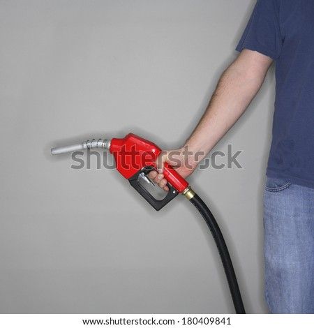 man in blue holding red gas hose and nozzle  - stock photo