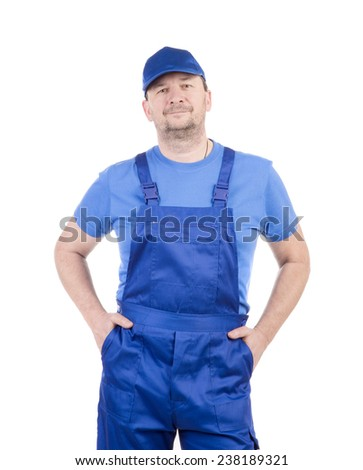Man in blue overalls with hands in pockets. Isolated on a white background. - stock photo