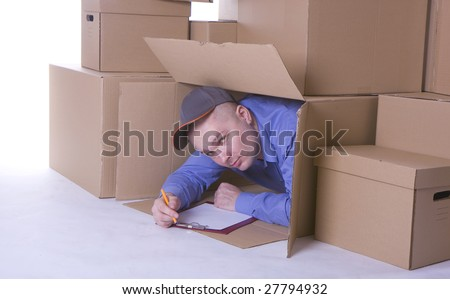 man in blue shirt and baseball cap looking out of carton box and writing on clipboard