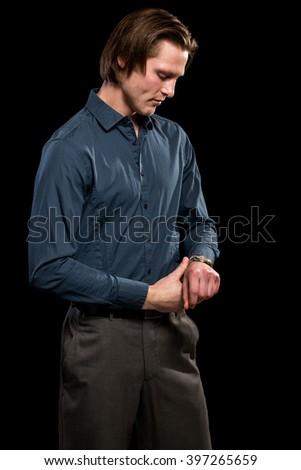 Man in blue shirt and grey slacks. Studio shot over black. - stock photo