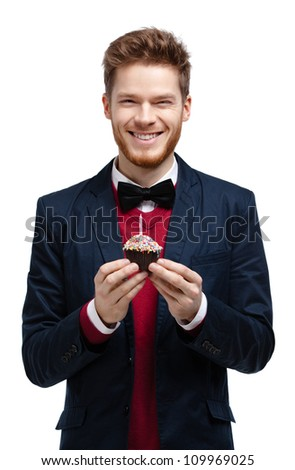Man in blue suit with bow tie holds small tart, isolated on white - stock photo