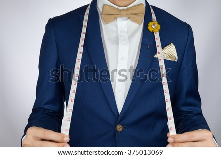 Man in blue suit with coffee cream bow tie color, flower brooch, and dot pattern pocket square carry measurement tape - stock photo