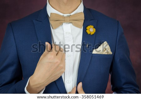 Man in blue suit with coffee cream bowtie color, flower brooch, and dot pattern handkerchief, close up - stock photo