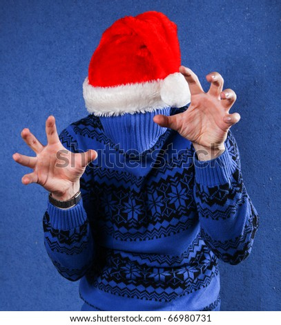 Man in blue sweater and red chrismas hat at blue background - stock photo