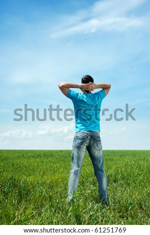 man in blue t-shirt standing on green meadow - stock photo