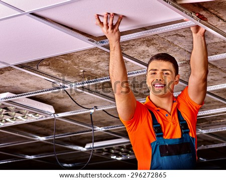 Man in builder uniform hand up  installing suspended ceiling - stock photo