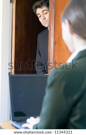 Man in business attire nosing around a doorway into a room where a female colleague is working - stock photo