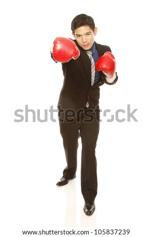 Man in business attire wearing boxing gloves and throwing a punch (on white)