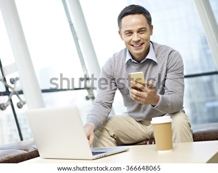 man in business casual wear looking at camera smiling while using mobile phone and laptop computer in office. - stock photo