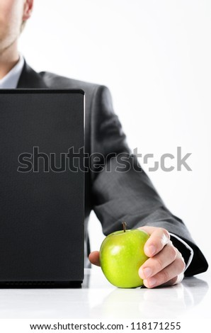 Man in business suit behind a laptop holds bright vibrant apple in hand, symbolising new ideas and fresh concepts or healthy lifestyle in the office - stock photo