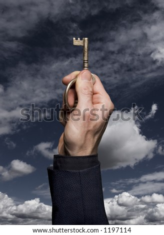Man in business suit holding an antique key against a blue sky with clouds. - stock photo