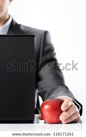 Man in business suit holds bright vibrant apple in hand, symbolising new ideas and fresh concepts or healthy lifestyle in the office - stock photo