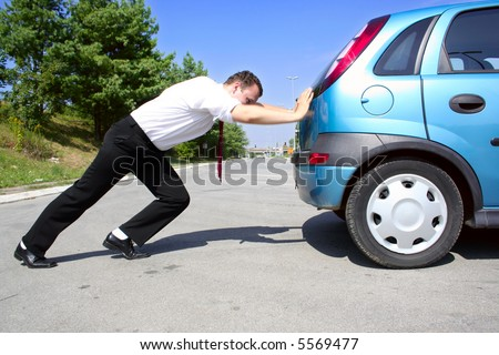 Man in business suit pushing a broken car or a car out of gas - stock photo