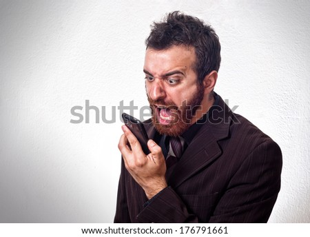 Man in business suit shouting into his mobile phone. Business concept - stock photo