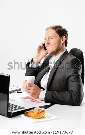 Man in business suit talks on mobile cell phone while drinking coffee and eating croissant pastry at his desk with laptop and documents - stock photo