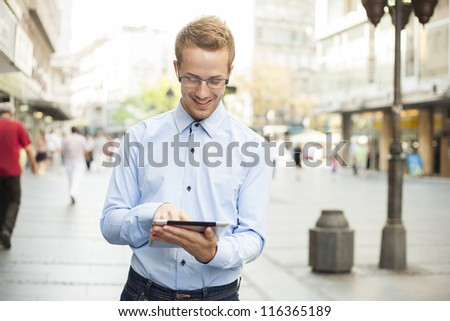 Man in Business suit using tablet computer in public space - stock photo
