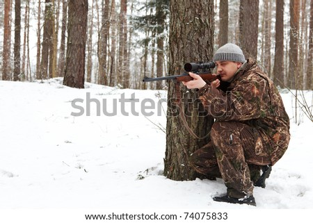 Man in camouflage aiming with sniper rifle at winter forest. - stock photo