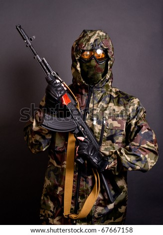 man in camouflage clothing holding gun - stock photo